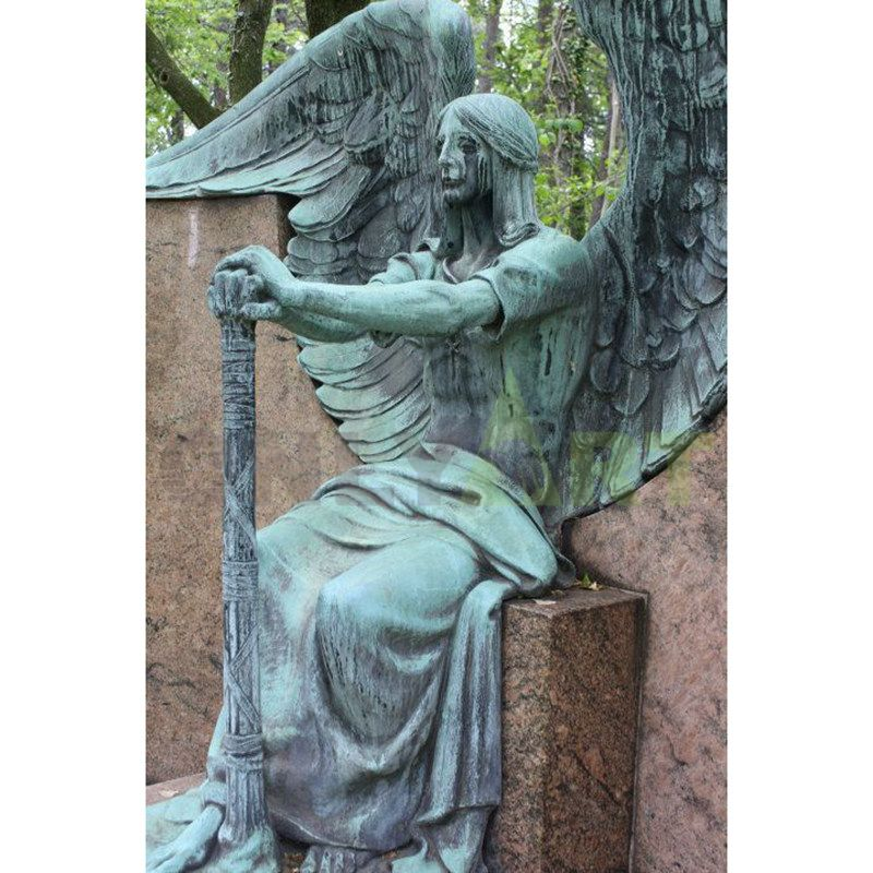 A bronze statue of a weeping angel holding a sword