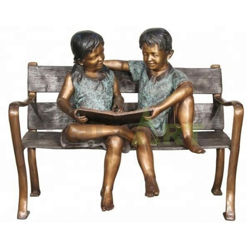 A sculpture of two children reading together on an apartment bench