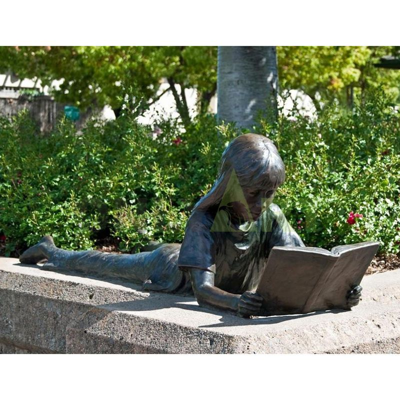 The girl leans on the stone and looks at the book in her hand with relish