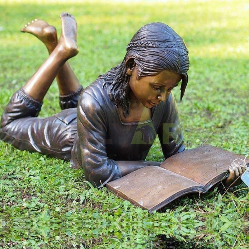 The little girl is reading a book on the lawn
