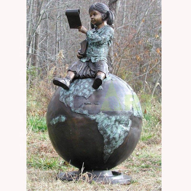A little girl sitting on a globe