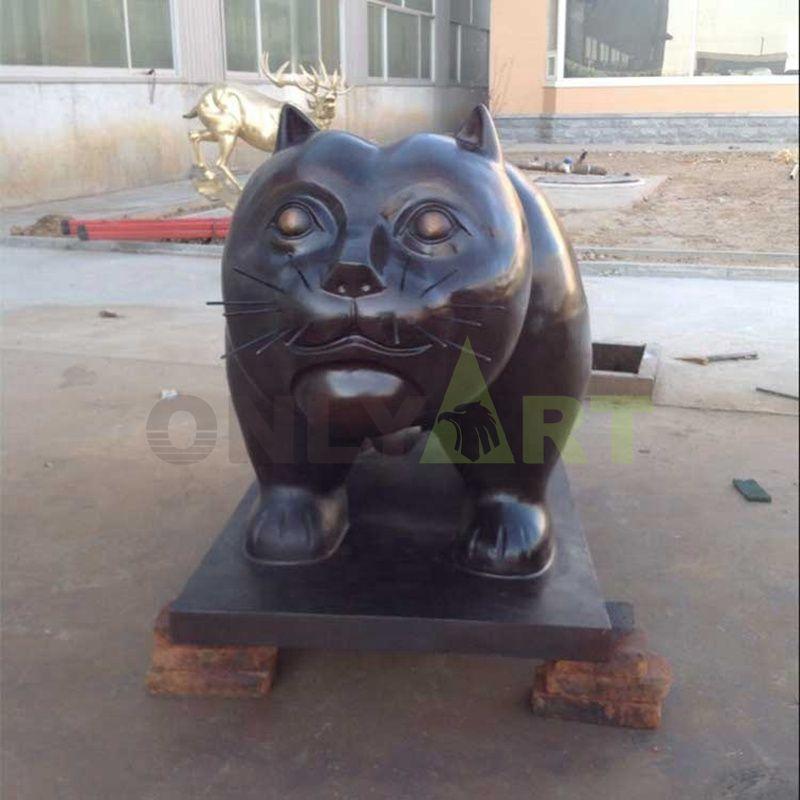Big black big-headed cat with big eyes staring at you
