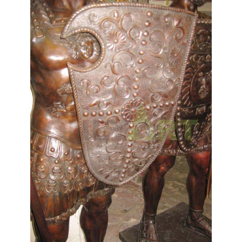 .A Bronze statue of a Spartan helmet holding a shield at the waist