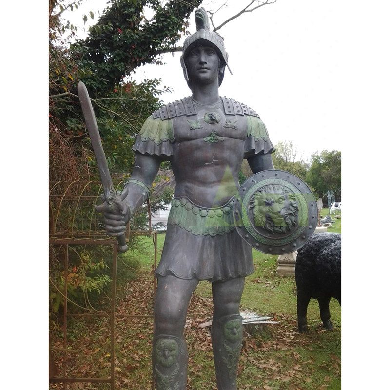 The Spartan leans over a heavily armed bronze statue