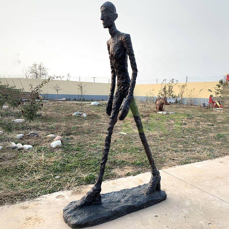 A black bronze statue of a man strides forward