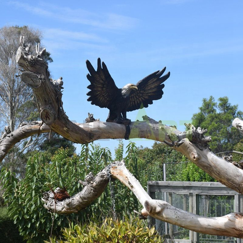 A bronze eagle with wings spread on a branch