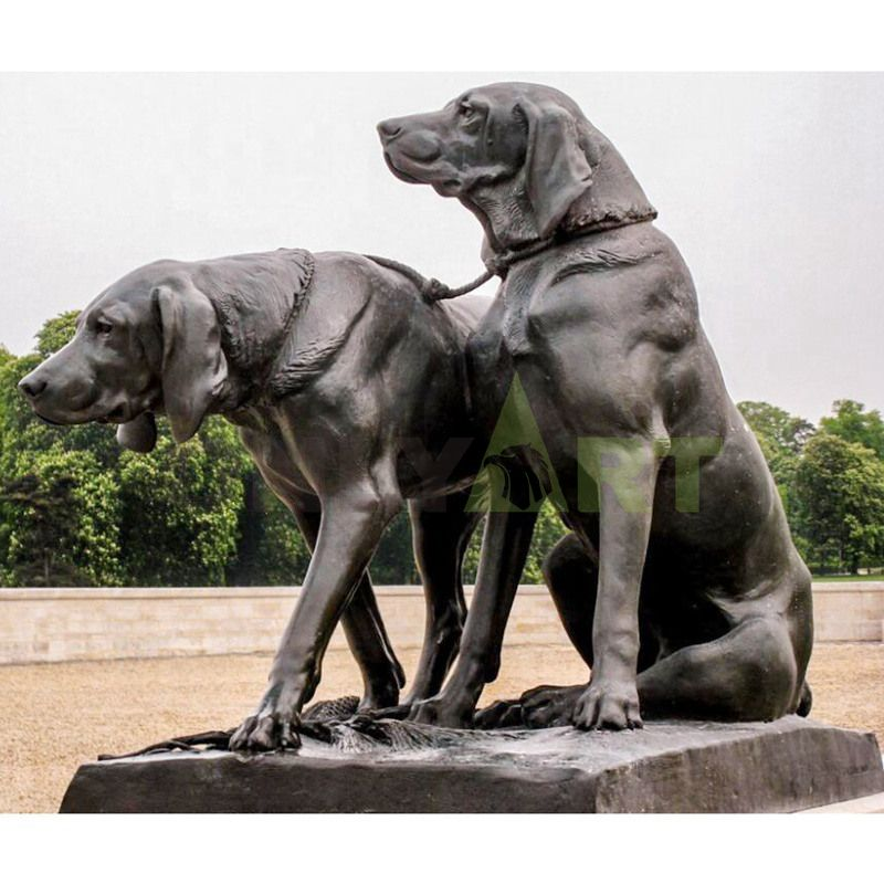 . Sculpture of two dogs on a leash in a park