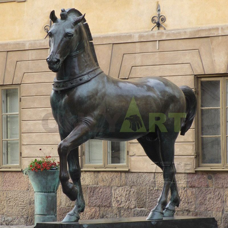 A statue of a horse in front of a large manor