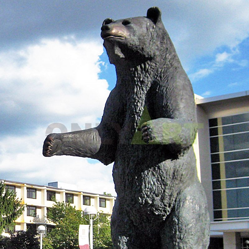A bronze sculpture of a brown bear carrying a suitcase for a trip is for sale