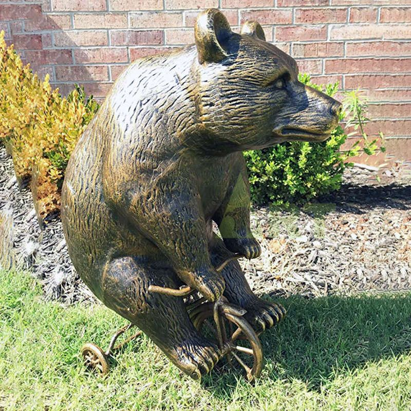 A bronze sculpture of a brown bear riding a bicycle is on sale