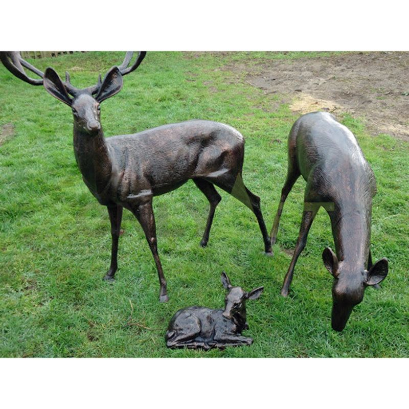 A family of three elk on the meadow. Bronze sculpture