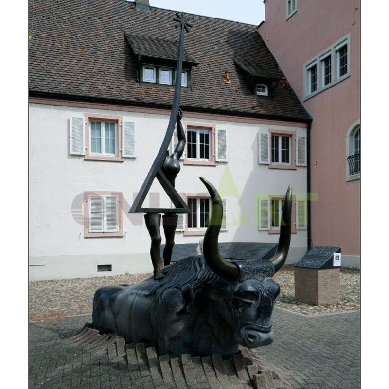 A geometric statue of a woman standing on a bull