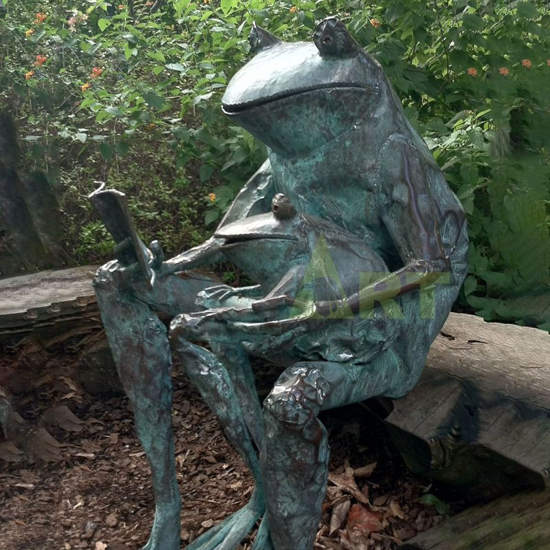 A bronze statue of a frog reading a book