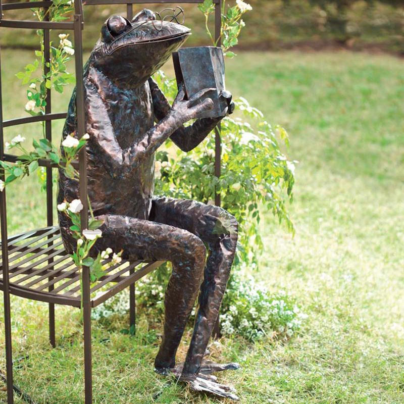 A sculpture of a frog sitting on a wicker chair holding a book