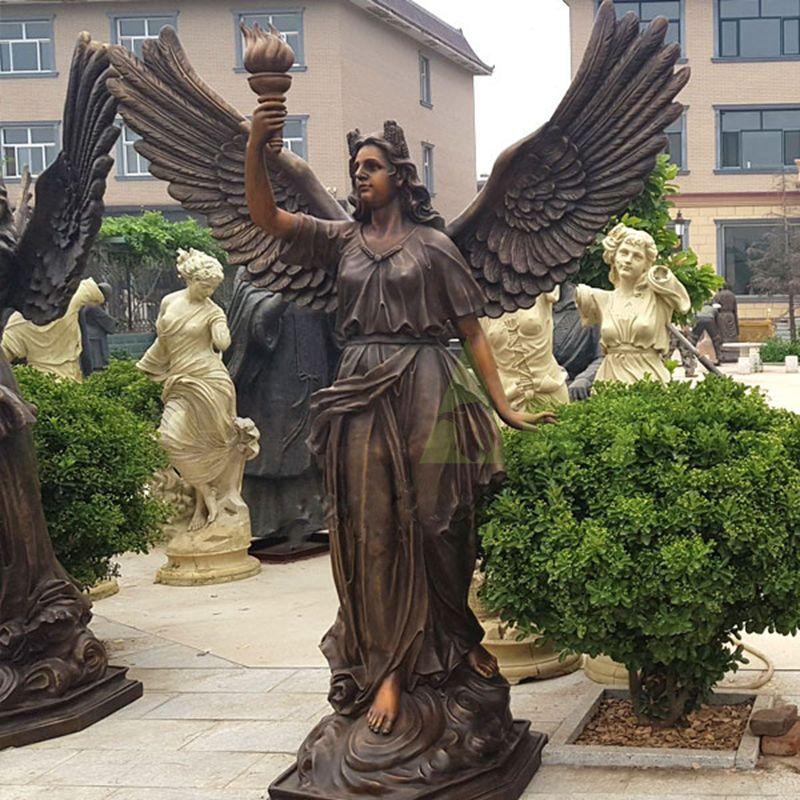 Life-size bronze sculpture of an angel holding a torch